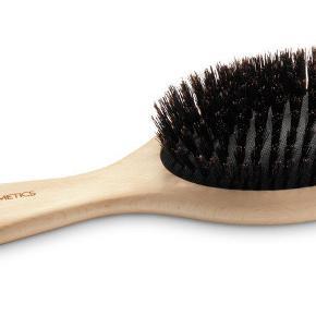 Lækker hårbørste fra M. Cosmetics i FSC-certificeret bøgetræ med ergonomisk udformet skaft.  Børsten er med ægte vildsvinehår, der fordeler hårets naturlige olier og giver et glansfuldt hår. Pga. rene naturhår er børsten særlig skånsom og god til udredning af fx hair extensions.