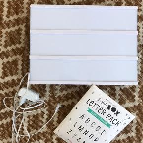 A little lovely company, lightbox lampe i hvid, A4 størrelse.   Inkl. strømkabel og pakke med 85 bogstaver/tegn.   Perfekt til boligindretningen eller måske som hyggelig lampe på børneværelset.   Fejler intet. Står som ny.