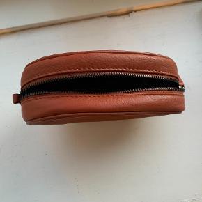Bumbag med tilhørende hank, der kan udskiftes til ens behov. Derudover er der hanke til at tasken kan sættes fast i ens bælte, som gør den perfekt til festivals og ferier  Farven er burned orange og går godt med både lyse og mørke farver