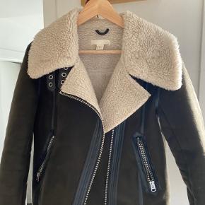 """Lækker jakke fra HM i en mørk army farve. Jakken er forret og kraven kan tages op som vist på andet billede. Der er to lommer og """"læder"""" detaljer. I en super stand."""