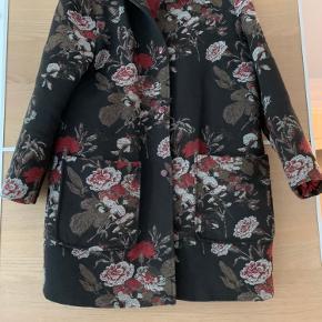 Overgangsfrakke med fint blomstret mønster. Har to lommer foran og en lomme på indersiden ved venstre bryst.  Er brugt, men fremstår i rigtig god stand.  Køber betaler fragt.  Byd gerne 🌸