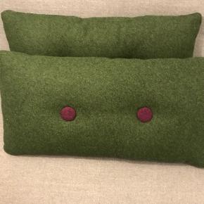 To puder fra HAY i mørkegrøn filt sælges. To knapper på hver side af puderne. Hvor de er lysegrå på den ene side og lilla på den anden.