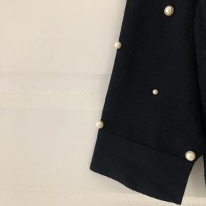 Finstrikket mørkeblå bluse fra Zara med perler på ærmerne. Stumper på håndleddet. Løs pasform, kan også passes af en S.   Vasket og brugt få gange. Sælges da jeg ikke får den brugt. Kan hentes på Nørrebro eller sendes med DAO.
