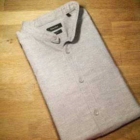 Meget meget smart Slim Fit skjorte med afslappet Kina krave fra Calvin Klein. Nypris: 1100 Stand: Praktisk talt som ny.  Se også alle mine andre annoncer med mærkevarer af høj kvalitet og stand til vanvittigt lave priser.