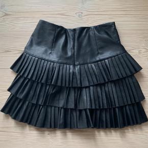 Varetype: Fræk Charlston mini/midi nederdel i Fabric Learher Farve: Sort  Super cool fake lædernederdel fra Muthe. Der står str 38  i den, men jeg vil nærmere sige str 40. Måler 40 cm i livet og den er 47 cm lang. Lynlås bagpå.