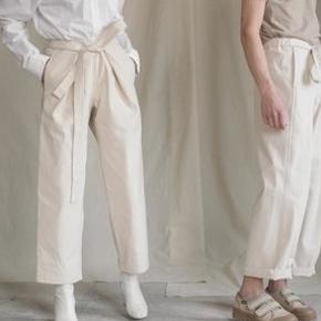 Bukser fra Aure. Unisex -bukser kaldet 'Atelier Trousers' i farven Cream. De er lavet i ufarvet bomulds kanvas og derfor i lækker tyk kvalitet. Kan bruges både af kvinder og mænd. Størrelsen hedder M-L.  Der står dette om str. på deres hjemmeside: M-L: Inseam (no fold): 73 Hem width: 23 Thigh width: 41 Seat width: 60 Waist: The waist is adjustable and will fit many sizes, also depending on how you wear the trousers (at the waist or on the hips).  For women M-L will fit sizes 36-42 For men M-L will fit sizes 46-52