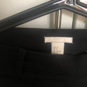 Fine sorte bukser. Lukkes med lynlås i siden. Lille slids ved benene.