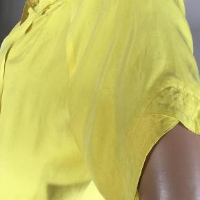 Virkelig lækker top i fed, klar gul silke fra Custommade. Korte ærmer med fin folde-detalje på oversiden + syninger. Snører ved halsudskæring og samme syninger rundt i halsudskæring som ved ærmeafslutning. Vasket efter køb og prøvet på nogle gange, men aldrig kommet i brug - lidt for lille til mig ... Top i fed silke. Farve: Gul Oprindelig købspris: 1200 kr.  Sendes gerne på købers regning : DAO 39,-