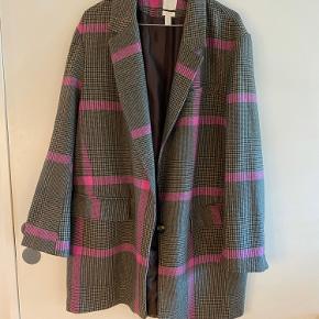 Let og oversized blazer jakke i en uldblanding fra H&M. Klassiske tern med lyserøde striber for kontrast. Str. M. God som overgangsjakke.