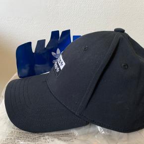 Sort Adidas cap / kasket i str one size. Materiale r poly og bomulds mix Regulerbar strap / strop bagpå. Købt i UO forår 20 - til 220 aldrig brugt, så stadig med mærker / tags! Hvis afhent 125