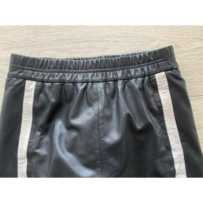 Flotteste lammeskinds nederdel fra InWear  - str. 38 - næsten som ny - elastik i talje 2x37-47 cm i taljen  - 53 cm lang  - 2 hvide striber foran  - blødt lammeskind - glat for indeni  Nypris 1799,-