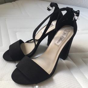 Sorte sandaler med 10 cm blokhæl. Sandalen er i ruskind og er imprægneret, og tåler derfor vand (i moderate mængder), støv og snavs. Indersålen på den venstre sandal har løsnet sig lidt, men det kan ikke mærkes (se billede 4). Brugt én gangKan afhentes i Give. Hvis pakken skal sendes, skal køber betale fragten
