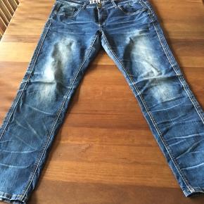 Skønne Veto jeans med 3-D og slid effekter i rigtig god stand.  Model: VE154035 regular fit med slim ben. Benlængde 32. Modellen er frontskåret, hvilket betyder, at en ekstra syningen langs benene er trukket lidt ind over låret, så de optisk synes smallere.  Syningerne er mange steder dobbelt med hver sin farve - orange og hvid - som giver disse jeans et super cool look.   Disse jeans lukkes med metal lynlås og 2 metal knapper med Veto logo.  Der er 2 baglommer, 2 skrålommer foran + en lille møntlomme. Linningen er fast, bred og med bæltestropper og den er højere bagpå, og er med til at giver en gode pasform som Veto er kendt for.   Kvalitet: 99% Bomuld, 1% Spandex. De er fremstillet i en god kraftig bomuld med en lille smule stretch, så de kan give sig yderligere 1-2 cm.   Mål: Indvendig benlængde: ca. 80 cm. Talje: ca. 104 cm. Lår: ca. 72 cm.  Bukserne er angiveligt lidt små i størrelserne.  Pris-ide: 250 kr. - men giv et bud.