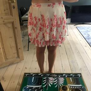 Smuk plisseret nederdel med blomster.  Er en normal str. 38 Har lynlås i siden.  Brugt en enkelt gang.  Bytter ikke.  Kan også afhentes på Frederiksberg eller Lyngby ☺️