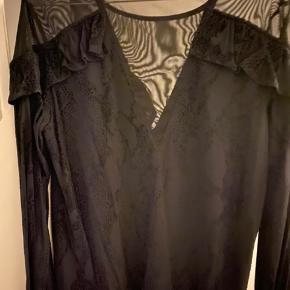 Flot bluse med transparent stykke for og bag.