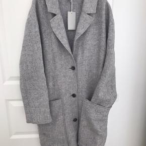 Uld-frakke i lys grå, oversize= dejlig rummelig; der er plads til en tynd dunjakke el. stik indenunder 👌 Passer en 38/40  Den er brugt et par gange men i meget velholdt stand; ingen fnuller/fnug ✅ Modtager betaler porto