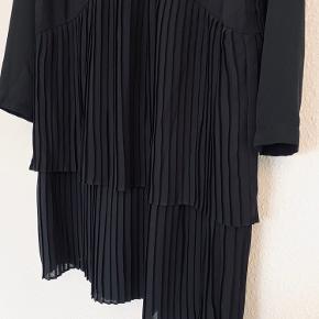 Utrolig fin plisseret kjole med lange ærmer og v-hals. Kjolen falder rigtig flot. Har ikke været brugt. Kan passes af small og medium.