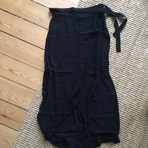 """Nederdel med """"slå-om"""" effekt - og bindebånd øverst. Perfekt til strømpebukser, støvler og en stor strik."""