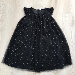 Sort kjole med sølvglimmer stjerner, str. 128, H&M, næsten som ny. 10% af prisen går til Kræftens Bekæmpelse (Team Vejdik, Stafet For Livet) Se mere på mostermette.dk (IG851)