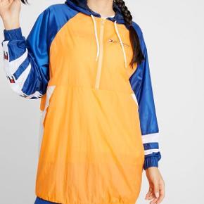 Mega fed Windbreaker -kjole i den lækreste kvalitet .  Tommy Sport !  Lårkort Hætte med løbegang, lommer med knap og elastik i ærmekant.  God vid pasform  Tynd for . Perfekt til fitness eller en sommernat  Str M  82 cm i længden  Farver : Hvid / blå / orange   Aldrig brugt  Np 1095,- stadig med mærker   Afhentes privat eller sendes med DAO på købers regning
