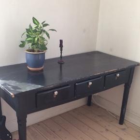 Smukt sort skrivebord med patina, med hvide håndtag til de tre skuffer.
