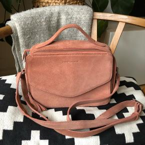 Daniel Silfen Holly taske i støvet rosa ruskind 🌺 Tasken har et stort rum med to mindre lommer, et stort rum bagved og en lomme med klap foran.   100% ruskind 22x17x9cm
