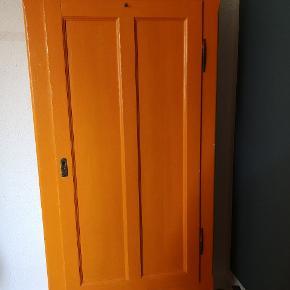 Ældre karlekammerskab sælges. Skabet er malet i en flot klar orange farve, men har en del knubs og skrammer. Deraf den lave pris. Der er fire hylder indvendigt i skabet.