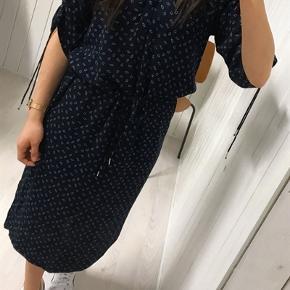 Kjole fra Soaked in Luxury i navy med hvidt print. Str. l. Kjole har halvlange ærmer, der med to indvendige bånd kan gøres  kortere med en rynkeeffekt. Kjolen har V-hals. I taljen er der et matchende bindebånd, som kan fremhæve taljen, hvis man ønsker en kjole med lidt mere facon. Kjolen går til under knæet. Stoffet er med en smule crepeeffekt. Lækker viskose-kvalitet. Nypris 800 kr. Brugt og vasket få gange.
