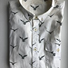 Just Junkies skjorte i knækket hvid med navy grønne fugle på. Brystlomme og lange ærmer.  Str.: L Materiale: 100% Bomuld (lækker lidt kraftigere kvalitet)  Brugt få gange.  Nypris ca. 499 kr.