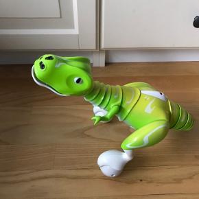 Interaktiv fjernstyret dinosaur. Kan bevæge sig, sige lyde og øjnene lyser. Lades op via USB kabel som medfølger .