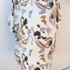 Råhvid, sort, rust og grå bluse Brystmålet er 2 x 64 cm Længde 72 cm