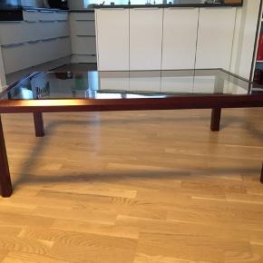 Sælger dette bord for mine forældre. Sofabord med glasplade fra IKEA. Det er pænt, men der selvfølgelig brugsspor. Str. L: 130 cm, B: 80 cm, H: 45 cm. Kommer fra et ikke ryger hjem. KOM MED ET BUD, MINDSTE PRIS 300kr. Kan afhentes i 3480 Fredensborg
