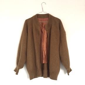 Lys brun vintage cardigan i 80% angora. Der er lidt slid i materialet øverst bagpå ryggen som vist på billedet. Dejlig varm og med inderfor. Passer str. S/M.