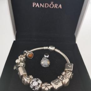 Pandora Moments slangekædearmbånd med 11 medfølgende vedhæng/charms. Det sidste vedhæng, som ligger separat, kan bruges til anden slags kæde. Kædearmbåndet i sig selv koster 449 kr. og hvert vedhæng har min. kostet 200 kr. og flere over 300 kr. Original æske medfølger.