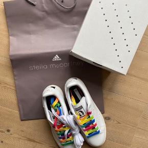 Et samarbejde mellem Adidas og Stella McCartney og den ikoniske Stan Smith sneakers i en str.39 1/3, hvilket svarer til en 38. Skoene er helt nye og i original æske, de kommer med klassisk hvide snørebånd samt multi farvede snørebånd.  Respekter venligst at jeg ikke bytter og køber betaler porto samt gebyr ved tspay.