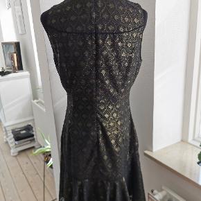 Smuk, sort Karen Millen kjole med gyldne detaljer. Str 40. Kun brugt 1 gang og er i rigtig flot stand. Køber betaler forsendelse med gls uden omdeling.