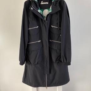 Model Terry Jakke med hætte med aftagelig kvast. Mid season model uden kraftig for. Fremstår i fin stand. Masser af lommer. Super fin regn jakke eller overgangs frakke.