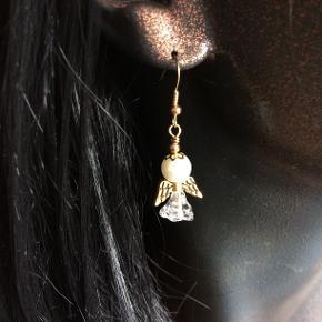 Øreringe med engel fra Designer USA  Søde engle med guld eller sølvvinger, som er udarbejdet af hvide glasperler, plastik tulipan-perler, forsølvet vinger, forgyldte vinger, forsølvet eller forgyldt ørering. Prisen er pr par  Perle-vedhænget måler 2,5 cm.  Jeg kan handle med mobilpay: Jeg sender gerne med post nord til din postkasse (+10 kr 5 dages leveringstid eller 29 kr 1 dags leveringstid), hvis du ikke kigger forbi og henter dem. Jeg kan handle via Trendsales med DAO pakkepost (+32 kr), hvor du afhenter pakken ved ønsket DAO udleveringssted.  mvh Lise