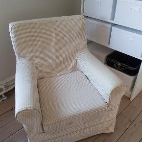 """Ektorp-lænestol fra Ikea med hvid- og beigefarvet tern. Betrækket har nogle pletter, som jeg ikke har forsøgt at fjerne. Jeg har selv købt lænestolen brugt med henblik på at ombetrække den, men får det ikke gjort alligevel. Man sidder rigtig godt i den, og nye betræk kan købes i Ikea. Gives bort efter """"først til mølle""""-princippet."""