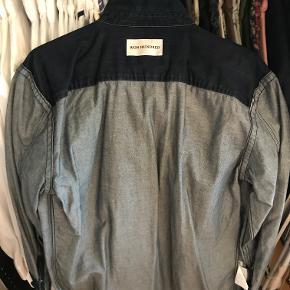 Mørkeblå denim skjorte fra danske Won Hundred. Skjorten er Str. M og har et regular fit. Skjorten er anvendt få gange, og fremstår derfor næsten som ny. Skjorten har samme farve både front og bag, og det ene billede er derfor mhp at vise farveforskellen på indersiden af skjorten vs. ydersiden.