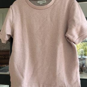 Helt som ny. Brugt et par gange. Enkel t-shirt i Rosa med glimmer.  Fra SS19 kollektionen. Nypris: kr. 400,-  Køber betaler porto og evt gebyr Handler gerne mobilepay
