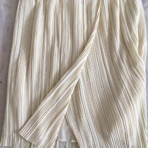 Rigtig fin plisseret nederdel i beige/pastel gul.   Jeg er str 36 selv, men den passer mig helt fint.