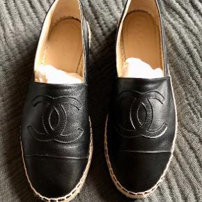 Chanel espadrilles i sort (str. 38). De er aldrig brugt og kvittering og boks medfølger. Nypris er 4.310 kr. og de er købt i Chanel butikken i København d. 17/6-2019. Jeg vil gerne så tæt på nypris, som mulig. Efter mange overvejelser har jeg valgt at sælge dem, da de ikke passer til min fod.