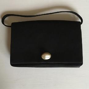 Fin vintage clutch med perlemors magnet knap. Hanken kan knappes af. Der er et stort og to små rum. Om taske er ægte silke og perlemor ved jeg ikke. Hvis man kigger nøje kan man ved lukningen se et lille buk, men der er ingen slid eller lign.  Kig forbi mine annoncer 😊 Altid mængderabat  Vintage Clutch / Selskabstaske Farve: Sort