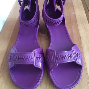 """Sandaler i hård gummi i mørke lilla.  De har """"lynlås"""" detaljer og lukkes med et """"bæltespænde"""" om anklen.  Har æske til"""