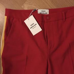 Helt ny - aldrig brugt - stadig med prismærke  Super fede Mads Nørgaard business bukser i rød med strib i siden.  Mads Nørgaard Sportina Panty Red. Sportina Panty er et par klassiske dress-bukser til damer. Bukserne har knaplukning i linningen, to skrå sidelommer og to baglommer samt bæltestropper. Panty har desuden kontrastfarvede bånd på siderne.  Helt nye - stadig med prismærke. Str. M  Sælges, da de er for store til mig.  Np - 850 kr Mp - 400 kr ekskl. fragt. #trendsalesfund