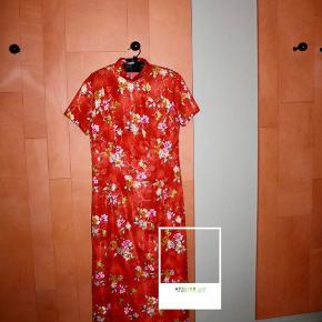 - BENYT 'KØB NU' FUNKTIONEN, VED KØB -  Rød gulvlange kjole med orientalsk mønster. Kjolen har korte ærmer, små slidser nederst i siderne og en høj halsudskæring. Den kan åbnes med en diskret lynlås venstre side og knappes med guldfarvet dekorative knapper henover det højre bryst.   ○ Mærke: Ukendt - intet indvendigt mærke ○ Størrelse: Ukendt - intet indvendigt mærke ○ Ærmelængde:  - Skulderbredde: 19,5 centimeter - Brystmål: 47 centimeter - Taljemål: 42,5 centimeter - Længde: 140 centimeter ○ Fit: Normal pasform. Størrelsen er cirka omkring en str. M (se mål) ○ Stand: Brugt og vasket et par gange ○ Fejl/Mangler: Ikke umiddelbart ○ Materiale: Ukendt - intet indvendigt mærke