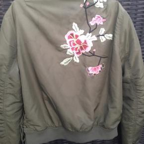 Virkelig sød overgangsjakke. Str Medium, svarer til str 38. Skøn grøn jakke med smukke broderier af blomster og kolibri.  Jakken er købt i Jennyfer i Nice, Frankrig.  Mange smarte detaljer