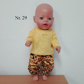 Nr. 29. Bukser med gule blomster og gul bluse. Syet i bomuld. Passer til Baby Born på 43 cm. Kan hentes i Horsens ellers sendes med Dao. Ved køb for min. 300 kr er der fri fragt.