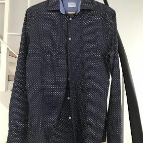 Varetype: Super flot ny skjorte Farve: Mørkeblå Oprindelig købspris: 499 kr.  Helt ny skjorte. Rigtig lækker kvalitet. Se evt. nærbillede af mønster på billede 2 og 3. Kan sendes eller afhentes i Århus C.
